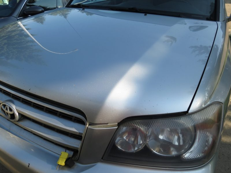 Road rash chipped paint on hood of a 2001 Toyota Highlander - Driver-side closeup