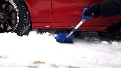 Using a portable telescoping shovel to dig car out from deep snow
