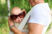 Closeup of baby boy in sling while his father is trying sunglasses on him, humorous aspect