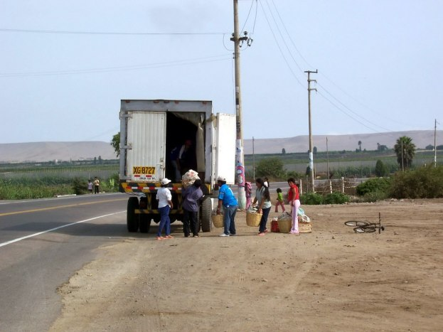 Farmer workers load produce into a truck on the Pan American Highway in Peru, South America
