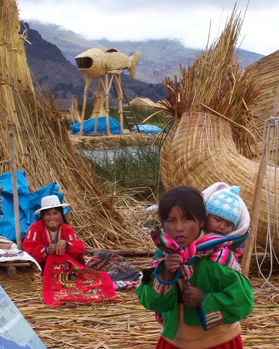 Uros woman and children on a floating island on Lake Titicaca in Peru, South America