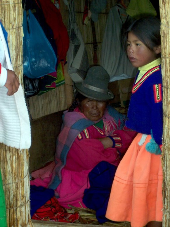 uros child and lady, floating island, lake titicaca, peru