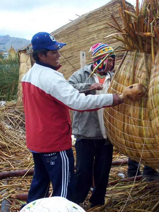 Uros men work on the side of a reed boat on a floating island on Lake Titicaca in Peru, South America