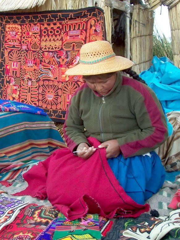 uros woman knits quilt, floating island, lake titicaca, peru