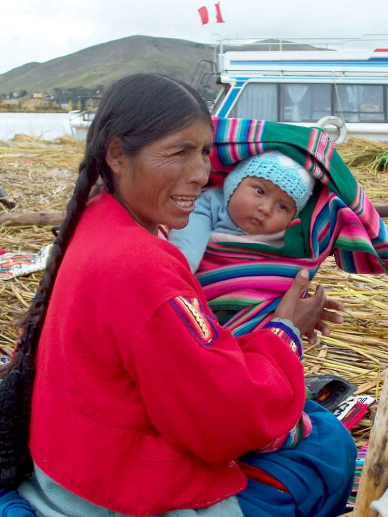 uros woman with a baby, floating island, lake titicaca, peru