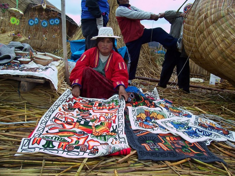 Uros woman selling blankets on a floating island on Lake Titicaca in Peru, South America