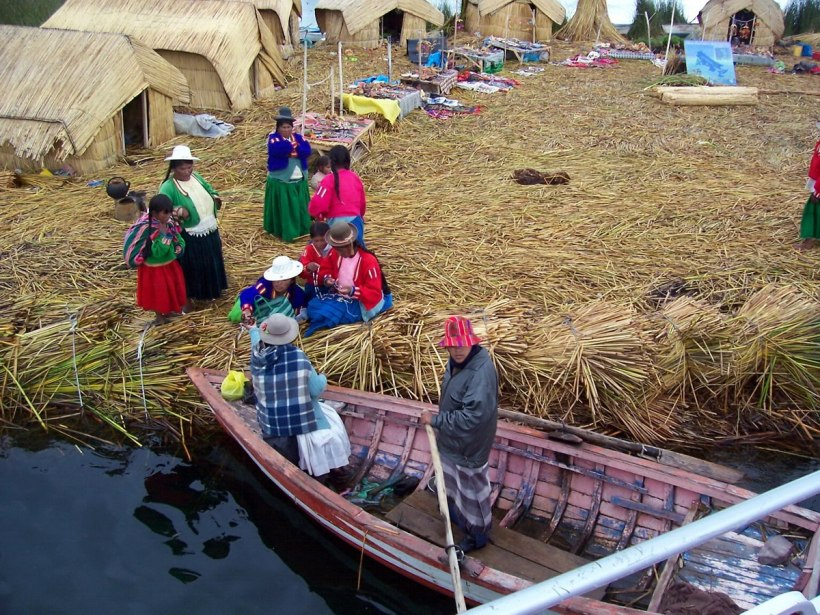 Uros woman on a floating island buying food from a boat on Lake Titicaca in Peru, South America