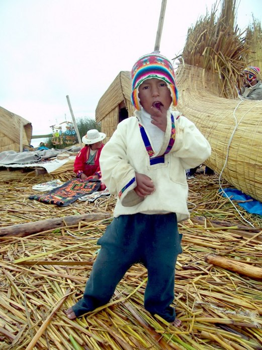 Young Uros boy on a floating island on Lake Titicaca in Peru, South America