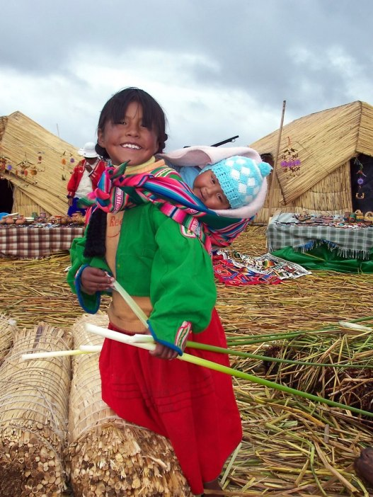 Young Uros girl carries a baby on her back on a floating island on Lake Titicaca in Peru, South America