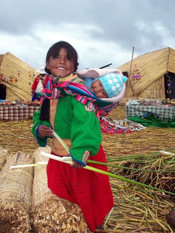young uros girl with baby, floating island, lake titicaca, peru