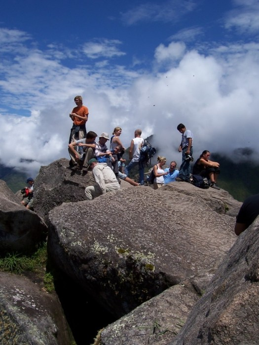 People sitting on rocks at the top of Huayna Picchu, Machu Picchu