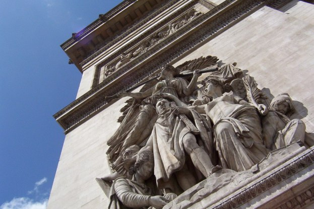 A low angle image of the Le Triomphe of 1810 sculpture on a pillar of the Arc de Triomphe in Paris, France.