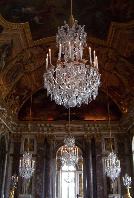 An image of chandeliers hanging in the Hall of Mirrors at the Palace of Versailles in France.