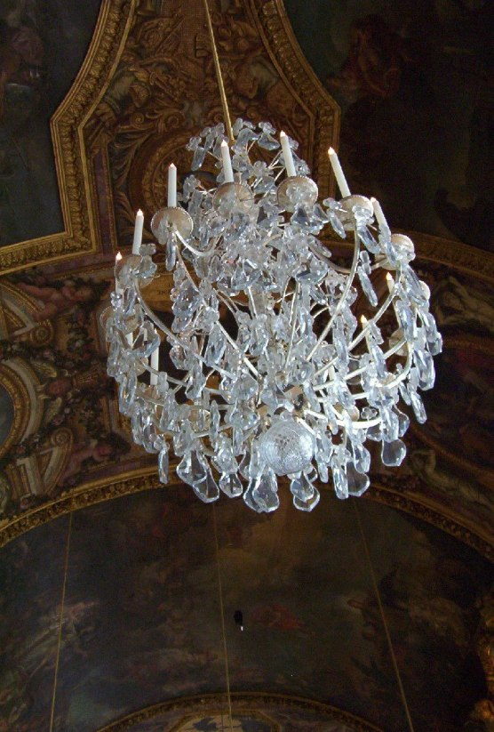 An image of a chandelier and ceiling in the Hall of Mirrors at the Palace of Versailles in France.