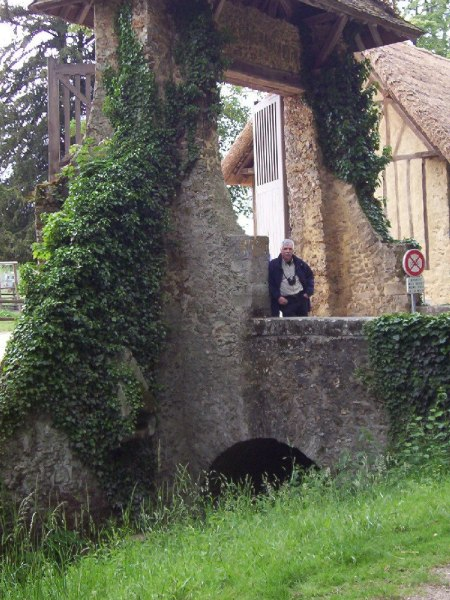 Marie Antoinette's estate gardens - Bob standing at entrance gate - France