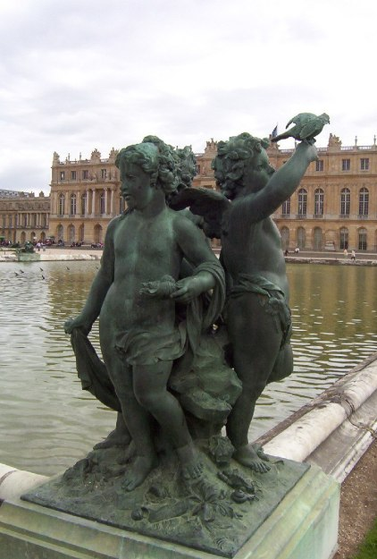 Palace of Versailles - Statue of children with a bird- along ornamental pool - France
