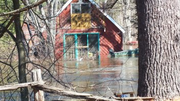 Big East River flood zone - flooded red colored home - Huntsville, Ontario - April 21 2013