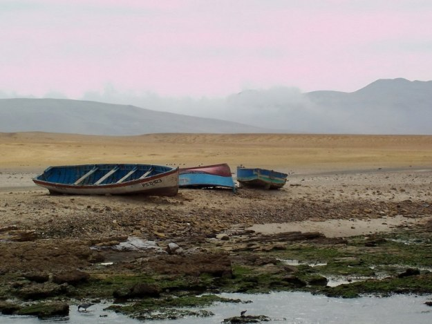 Boats on desert shoreline at Playa Lagunillas in Paracas National Reserve, Ica, Peru.