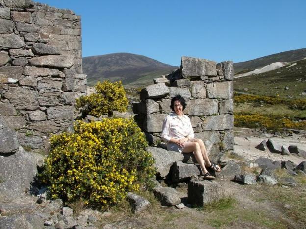 jean sits beside miners village ruins - glendalough - wicklow - ireland