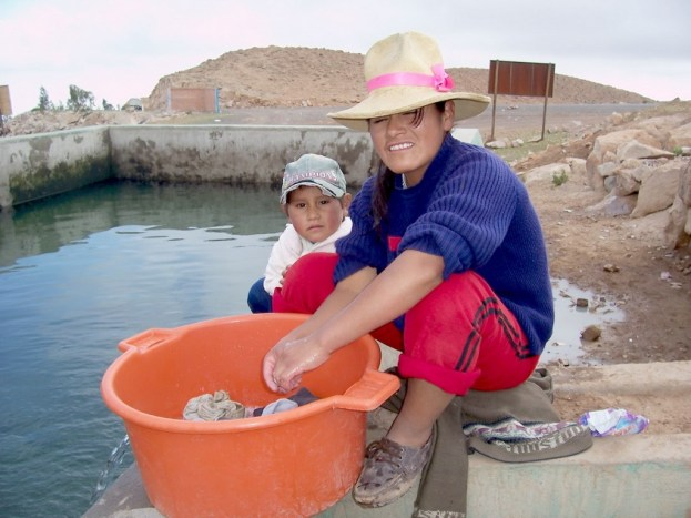Woman washes her clothes at the public reservoir in Nuevo Santiago, Peru, South America