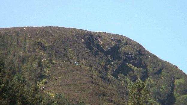 people climb up to prezen rock - wicklow mountains national park - ireland