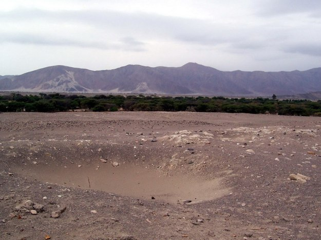 A pit in the desert at the Chauhilla Cemetery near Nazca in Peru, South America.