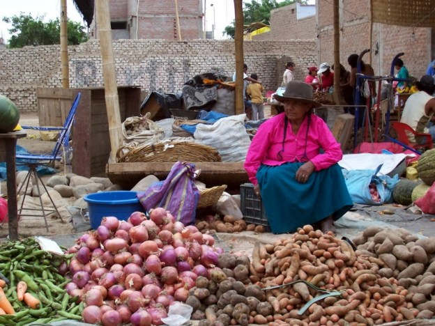Woman selling onions and potatoes in the street market in Nazca, Peru, South America