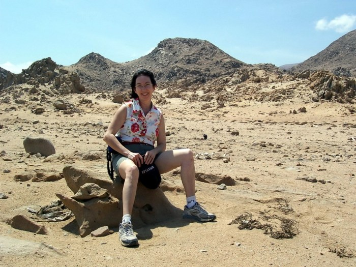 jean sits on rock in nazca desert in peru - frame to frame