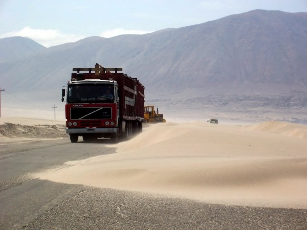 truck drives around sanddunes on pan american highway in peru - frame to frame