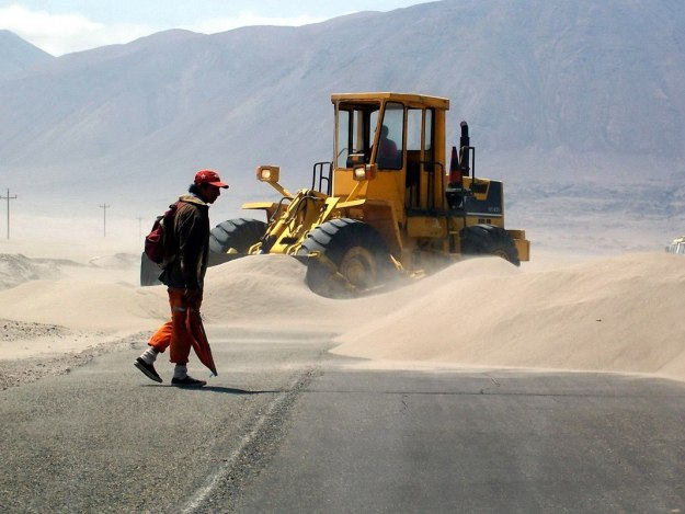 workers clear sand off pan american highway - peru