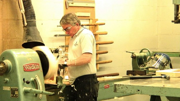 Image of a man carving a wooden mold at the Waterford Crystal plant in Waterford, Ireland. Photography by Frame To Frame - Bob and Jean.