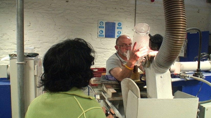 An image of Jean watching a master cutter cutting a vase at the Waterford Crystal factory in Waterford, Ireland. Photography by Frame To Frame - Bob and Jean.