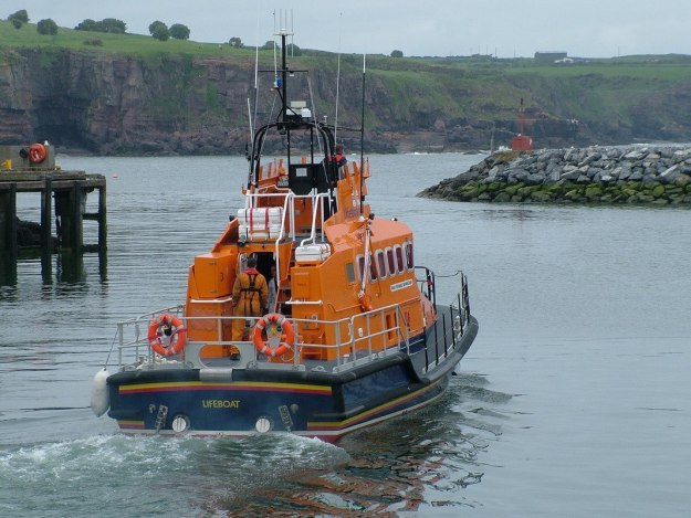 lifeboat leaves harbour from dunmore east in county waterford - ireland