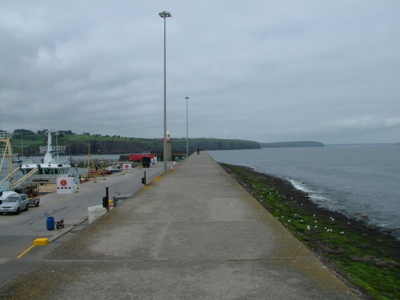 stormy clouds over harbour at dunmore east in county waterford - ireland
