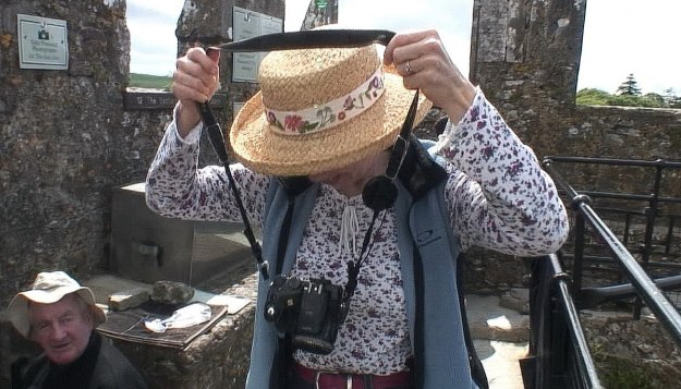 jean removes camera to kiss the blarney stone, blarney castle, ireland