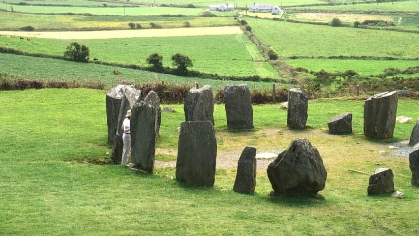 Jean stands among stones at the Drombeg Stone Circle in County Cork, Ireland.