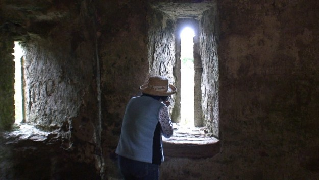 An image of Jean taking a picture through a window in the wall of Blarney Castle near Cork in Ireland. Photography by Frame To Frame - Bob and Jean.