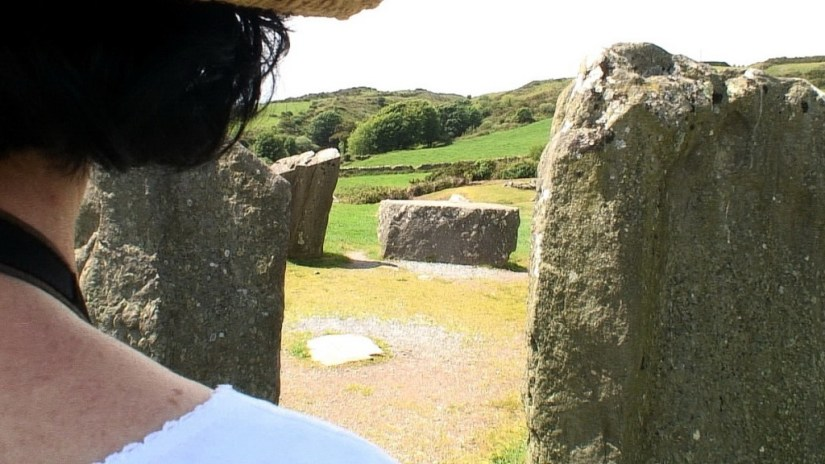 An image of Jean looks at the recumbent axial stone at the Drombeg Stone Circle in County Cork, Ireland. Photography by Frame To Frame - Bob and Jean
