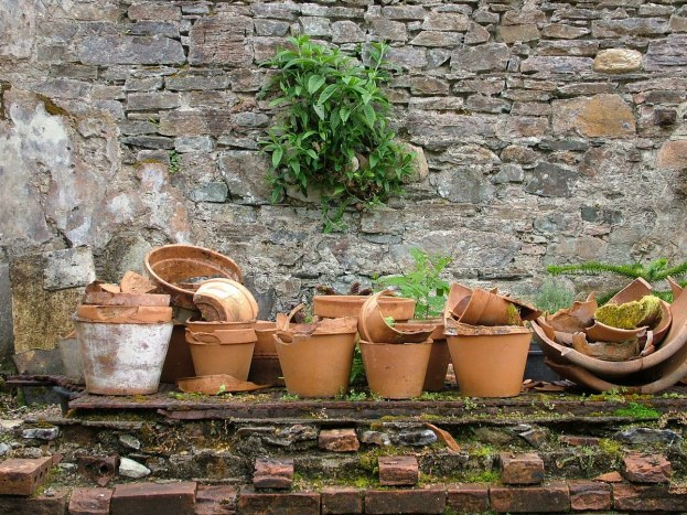 Broken flower pots and a stone wall in the Walled Victorian Gardens at Kylemore Abbey in Ireland