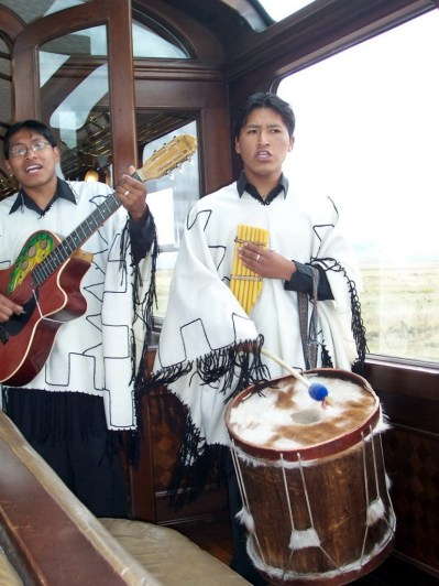 Musician plays a Bamboo Zampona Pan on board the PeruRail Andean Explorer train in Peru, South America