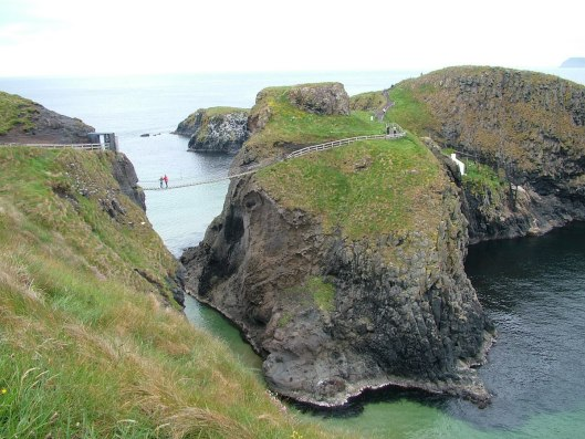 An image of two people standing on the Carrick-a-Rede rope bridge in Northern Ireland. Photography by Frame To Frame - Bob and Jean.