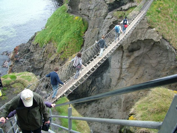 An image of people walking across the Carrick-a-Rede rope bridge near Ballintoy in County Antrim, Northern Ireland. Photography by Frame To Frame - Bob and Jean.