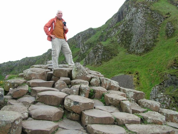 An image of Bob standing on the hexagon rocks at the Giant's Causeway in Northern Ireland. Photography by Frame To Frame - Bob and Jean.