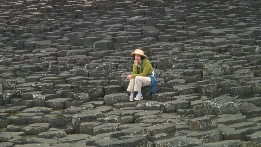 An image of Jean sitting among the hexagonal basalt columns at the Giant's Causeway, near Portrush, Northern Ireland. Photography by Frame To Frame - Bob and Jean.