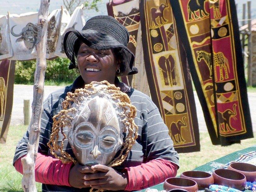 Woman holding Zulu face mask at craft market at the top of the Blyde River Canyon, South Africa
