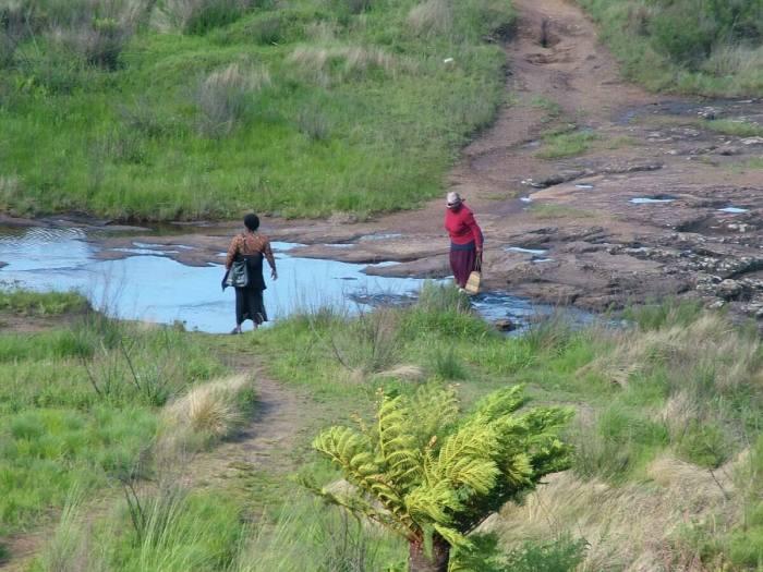 women cross ngwaritsane stream above pinnacle waterfalls, graskop, south africa, 2