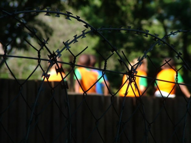 Children playing behind school razor wire in Sabie, South Africa