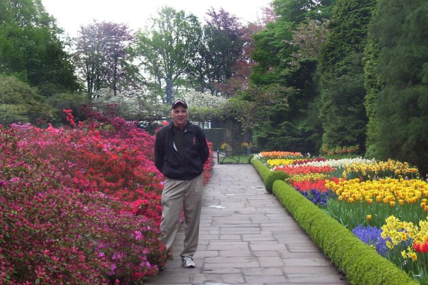 An image of Bob standing beside flower beds at Keukenhof Gardens near Lisse, in the Netherlands. Photography by Frame To Frame - Bob and Jean.