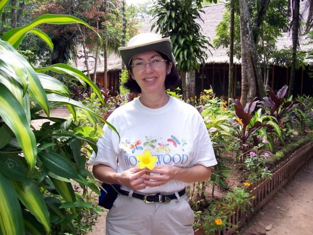 Jean holding yellow flower at Sandoval Lake lodge, Lake Sandoval, Amazon Basin, Peru