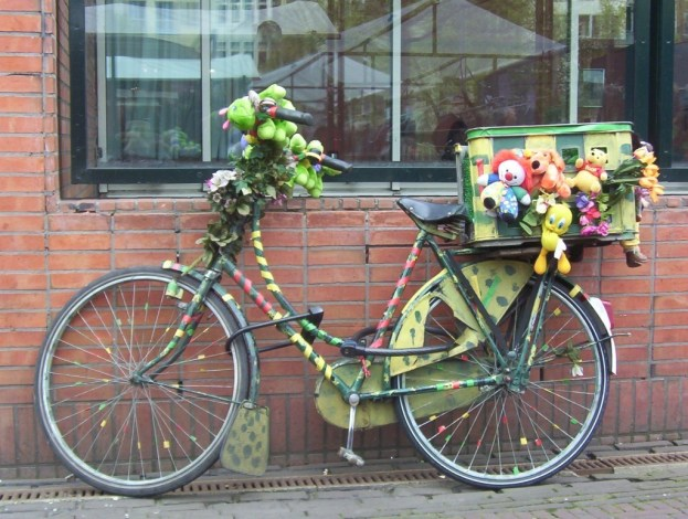 green colored bike with toys in amsterdam, the netherlands